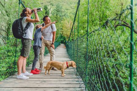 Family with small yellow dog standing on a wooden suspension bridge and resting 免版税图像 - 85011321