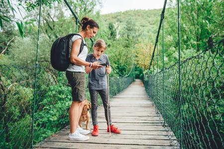 Mother and daughter standing on wooden suspension bridge with small yellow dog in the forest and using smart phone to navigate