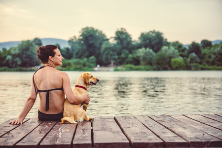Woman sitting with small yellow dog on dock