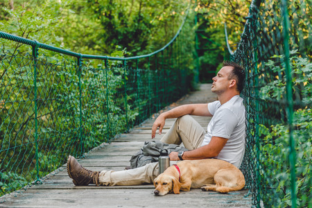 Hiker with small yellow dog resting on the wooden suspension bridge in the forest