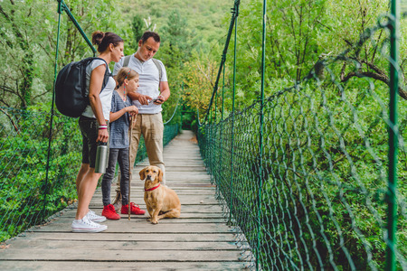 Family with dog standing on a wooden suspension bridge and using smart phone to navigate 免版税图像 - 85011298