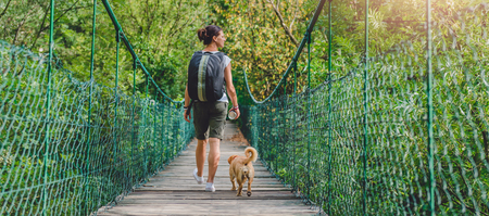 Women and small yellow dog walking over wooden suspension bridge in the forest 免版税图像 - 85011296