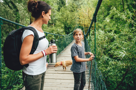 Mother and daughter standing on wooden suspension bridge with small yellow dog and talking