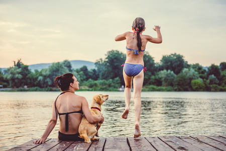 Mother and dog sitting on a dock and looking at daughter jumping into water 免版税图像 - 85011309