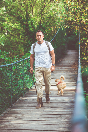 Hiker with small yellow dog walking over wooden suspension bridge in the forest 免版税图像 - 85011277