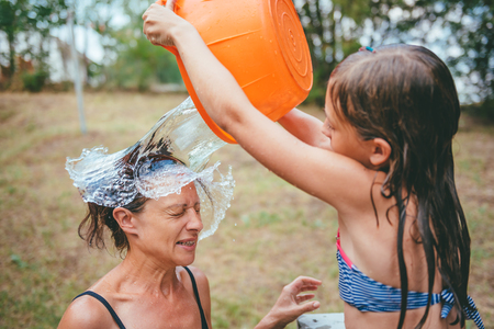 Mother getting splashed by a stream of water in her face Stock Photo