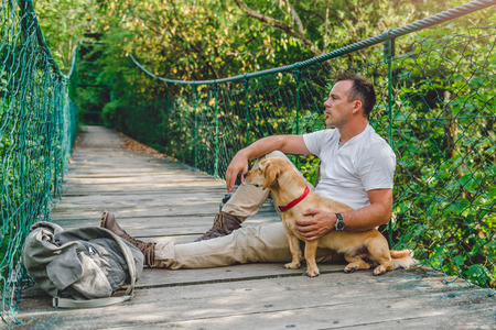Hiker with small yellow dog resting on the wooden suspension bridge in the forest 免版税图像 - 85011288