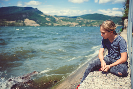Sad little girl sitting by the water on a windy day