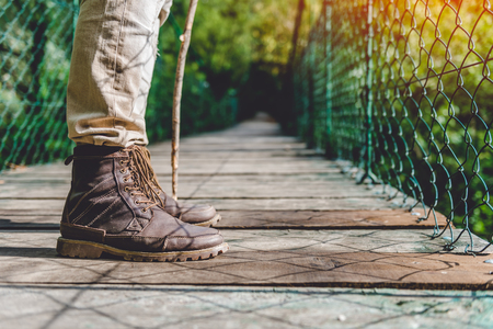 Hikers boots on the wooden suspension bridge in the forest