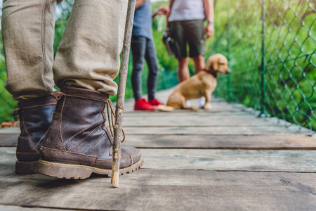 Family with dog standing on the wooden suspension bridge