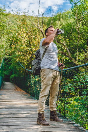 Hiker standing on the wooden suspension bridge in the forest and drinking water 免版税图像