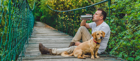 Hiker with small yellow dog resting on the wooden suspension bridge in the forest and drinking water 免版税图像