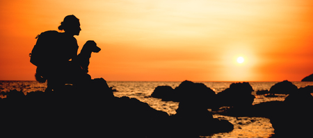 Woman with a dog hiking along the seashore during sunset 免版税图像