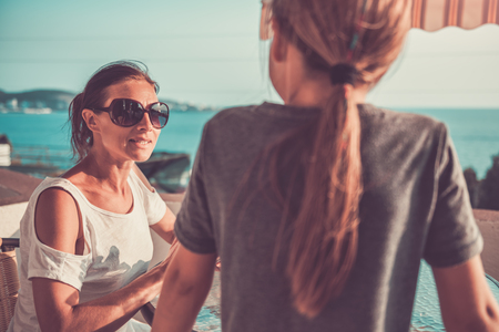 Mother wearing sunglasses talking with daughter on balcony