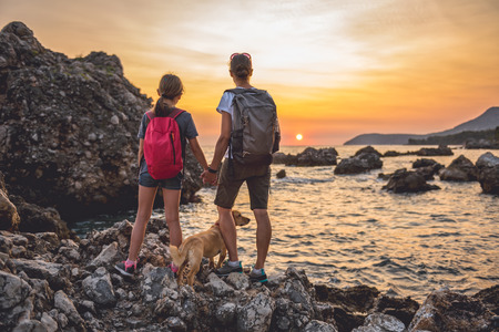 Mother and daughter with a small yellow dog hiking along the seashore during sunset 免版税图像