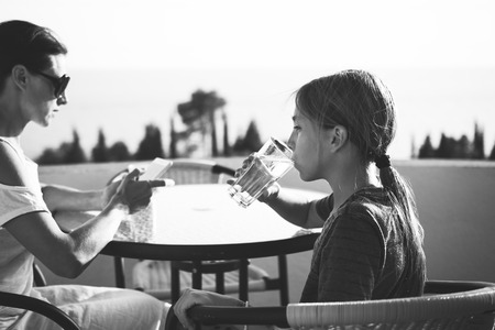 Girl sitting on balcony with her mother and drinking water  免版税图像