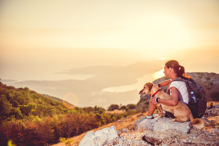 Woman with a dog sitting on a mountain and looking at a bay during sunset