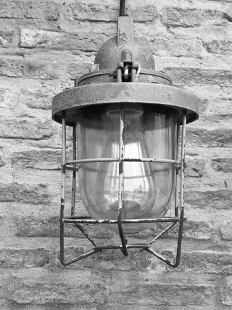 caged: Vintage caged inspection lampcontemporary style interior light, featuring metal cage, glass dome, wooden handle and leather hanging strap. White painted industrial brick wall background Stock Photo