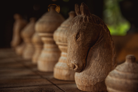 Black knight chess team on the wood board background.