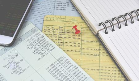 Red pin on book bank saving. Mobile screen treading.