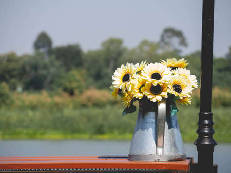 Flower pot shaped watering can and yellow plants placed by the river.