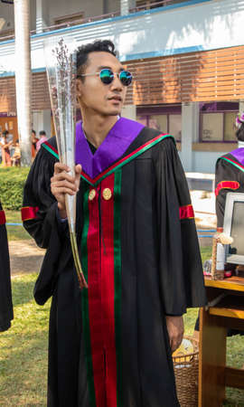 The graduate wore a gown from a university in Thailand. For graduation