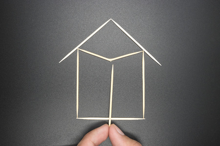 Toothpick, hand supporting a broken home