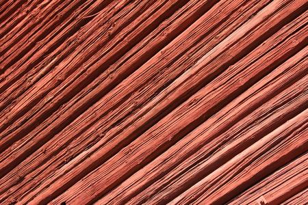 pared madera: Vieja pared de madera de color rojo en la luz del sol, torcida. Foto de archivo