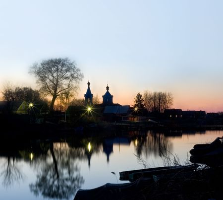 Rest and silence in village. Warm light from windows of houses and lanterns is reflected in a mirror of water. The silhouette of rural church towers above houses.