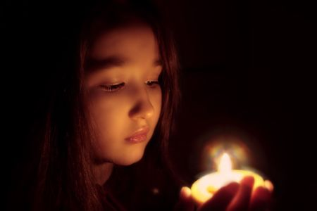 Portrait of the girl with a candle in hands. The spiritualised face . Mood of sacrament and revelation. Stock Photo