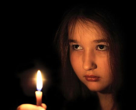 Portrait of the girl with a candle in hands. Eyes of the girl radiate force of character. Hardness of the decision. Confidence.