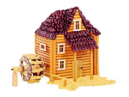 Watermill made from breadsticks, macaroni, beans, snacks and others different foods. Handiwork. Isolated on white background.