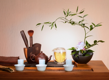 ikebana: Tea still life: flowers , kettle, cups, pile of dry tea.