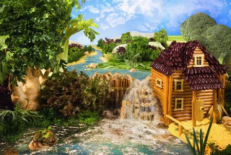 molino de agua: Paisaje con molino de agua hecha de palitos de pan, macarrones, bocadillos y otros alimentos diferentes. Obra. La imagen está hecha de múltiples archivos. Foto de archivo