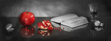 pomegranate in the form of heart with seeds of pomegranate symbolizes passion and sexy couple, and the open book symbolizes continuation of history Stock Photo