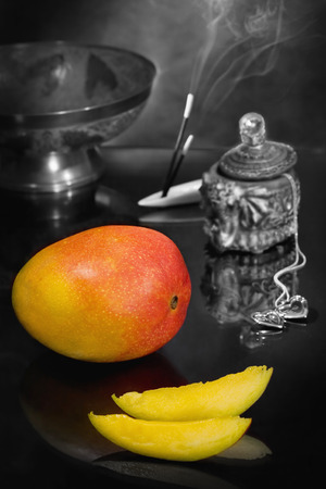 Theme of romantic evening for lover with flavors of the East. Two slices of mango in the form of boats symbolize a journey into the world of love, passion and pleasure. Focus on the mango.