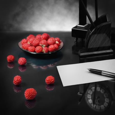 love image: First step in the recognition of love to hearts desire. Strawberry symbolizes voluptuousness; reflection clocks and a blank sheet of paper - anticipation. Focus on the pen and berries of foreground. Panoramic image from several pictures.