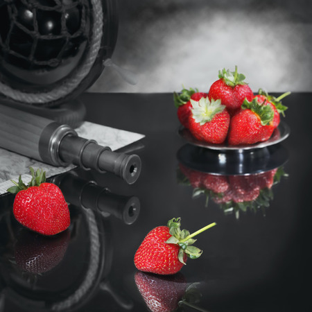 Imagination on a theme of search of the soulmate. The telescope and the map represent searches. Strawberry symbolizes temptation and fascinating communication. Focus on the berries of foreground. Panoramic image from several pictures.