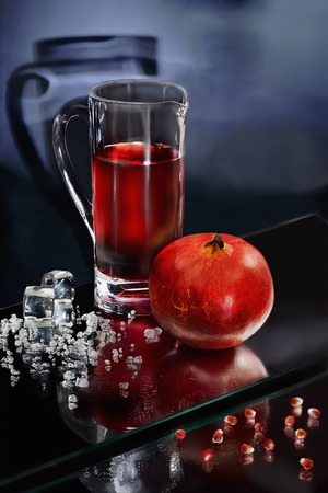 Still Life with a pomegranate juice and crushed ice.  Sharpness on the pomegranate and an ice crumb Stock Photo