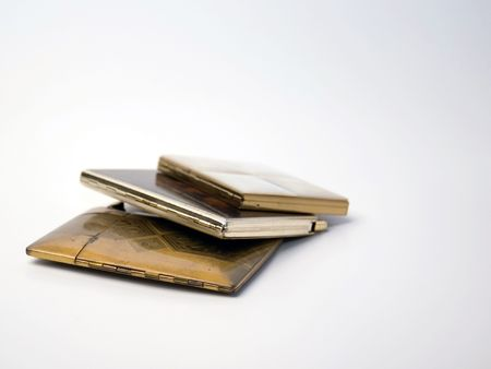 Three vintage cigarette cases on a white background.