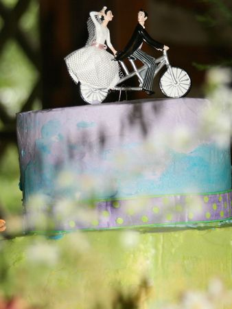 A colorful layered wedding cake, topped with the bride and groom riding a bicycle-built-for-two. photo
