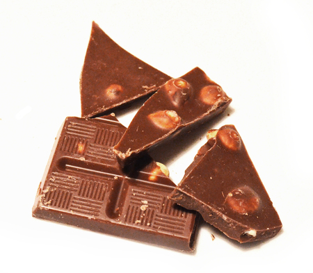Heap of broken chocolate hazelnut pieces on white background Banque d'images