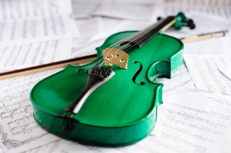 Green violin and musical score Stock Photo