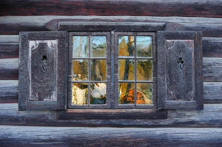 norwegian: Window of a traditional Norwegian hut with beautiful reflection Stock Photo