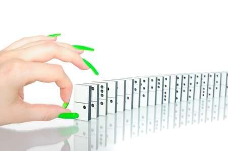 Womans hand with glamour nails going to show the domino effect photo