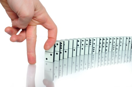 chain reaction: Mans hand going to snap the dominoes Stock Photo