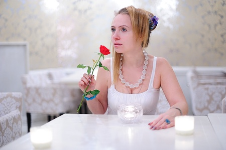Romantic girl with a red rose at a cafe Stock Photo - 10400696