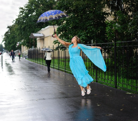 Girl flying with umbrella photo