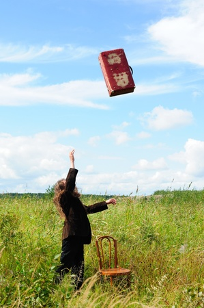 'young things': Man throwing his old suitcase into the sky