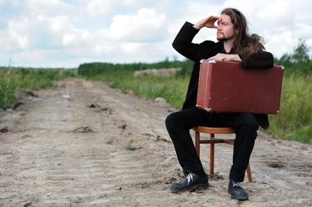 Homme avec une vieille valise attendre quelque chose sur la route Banque d'images